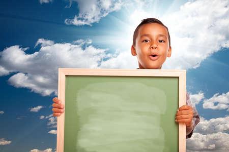 hispanic boy: Transferencia de datos de orgullosos hispanos Boy, holding de pizarra en blanco sobre el cielo azul y nubes con Sun.