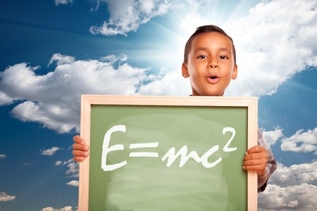 burst background: Proud Hispanic Boy Holding Chalkboard with Theory of Relativity Over Blue Sky and Sun Burst Clouds. Stock Photo