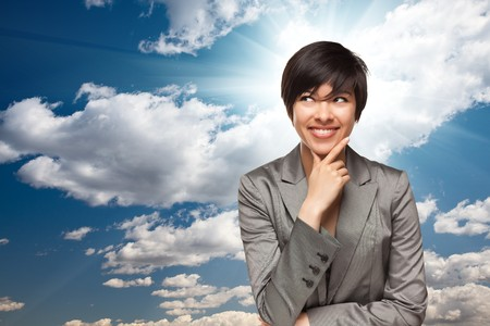 sun burst: Pretty Multiethnic Young Adult Woman Over Blue Sky and Clouds with Sun Burst Rays. Stock Photo