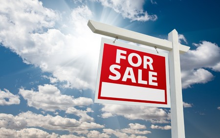 real: For Sale Real Estate Sign over Clouds and Blue Sky with Sun Rays.