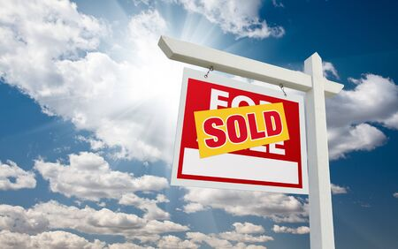 real estate sold: Sold For Sale Real Estate Sign over Clouds and Blue Sky with Sun Rays. Stock Photo