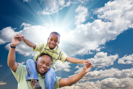 happy african: Happy African American Man with Child Over Blue Sky, Clouds and Sun Rays.