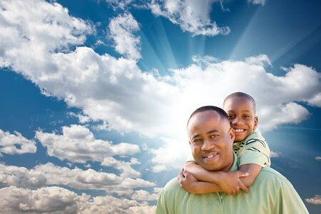 preadolescent: Happy African American Man with Child Over Blue Sky, Clouds and Sun Rays.