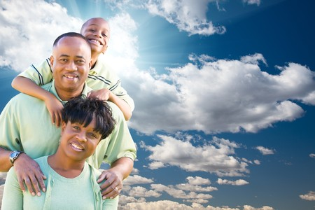 Happy African American Family Over Blue Sky, Sun Rays and Clouds. photo