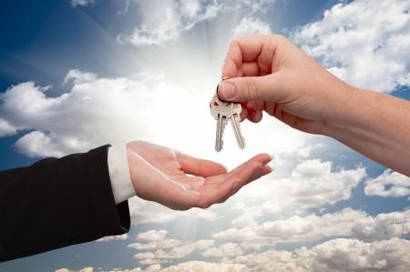 Klucze: PÅ'ci mÄ™skiej Hand dowiezienie klucze do Female Hand Dramatic Clouds i promienie Sun.  Zdjęcie Seryjne