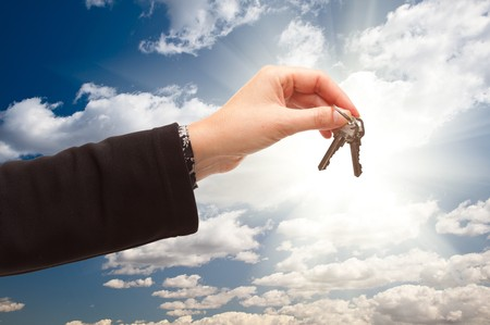 realty residence: Female Holding Out Pair of Keys Over Dramatic Clouds and Sky with Sun Rays. Stock Photo