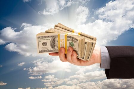 Male Hand Holding Stack of Cash Over Dramatic Clouds and Sky with Sun Rays. photo