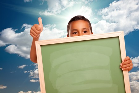 Proud Hispanic Boy Holding Blank Chalkboard Over Blue Sky and Clouds with Sun Rays.