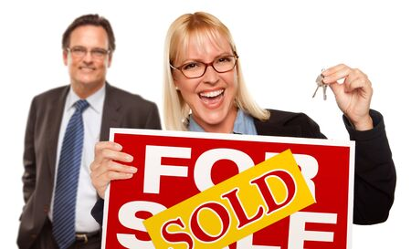 Man Behind with Attractive Blonde in Front Holding Keys and Sold For Sale Sign Isolated on a White Background. Stock Photo