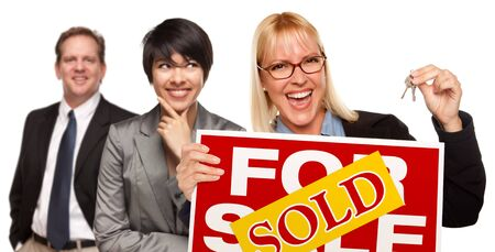 sales person: Real Estate Team Behind with Blonde Woman in Front Holding Keys and Sold For Sale Real Estate Sign Isolated on a White Background. Stock Photo