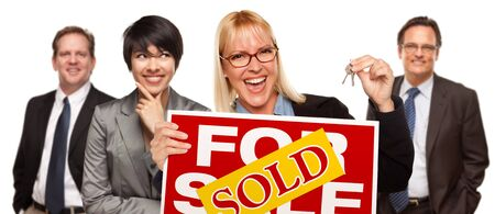estate: Real Estate Team Behind with Blonde Woman in Front Holding Keys and Sold For Sale Real Estate Sign Isolated on a White Background. Stock Photo