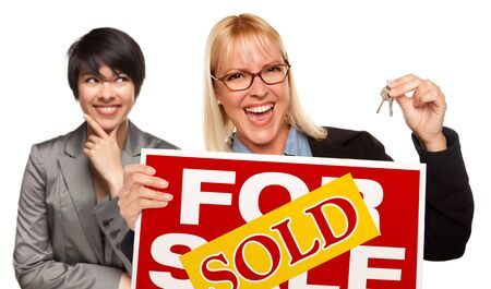 blonde hispanic: Hispanic Female Behind with Attractive Blonde in Front Holding Keys and Sold For Sale Sign Isolated on a White Background.