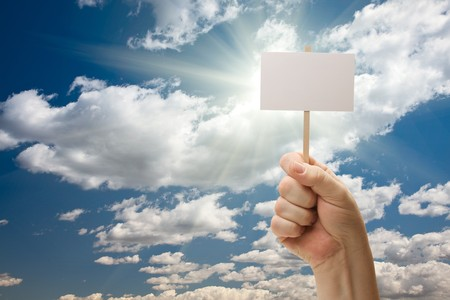 textfield: Man Holding Blank Sign Over Dramatic Clouds and Blue Sky with Sun Rays - Ready For Your Own Message on Sign and Over Clouds.