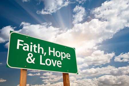 christian faith: Faith, Hope and Love Green Road Sign with Dramatic Clouds, Sun Rays and Sky.