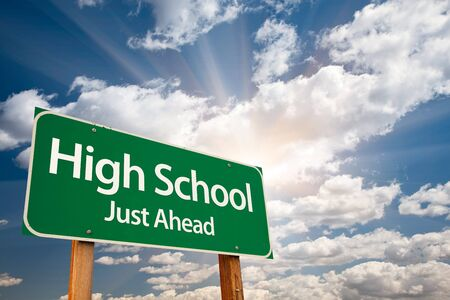just ahead: High School Just Ahead Green Road Sign with Dramatic Clouds, Sun Rays and Sky. Stock Photo
