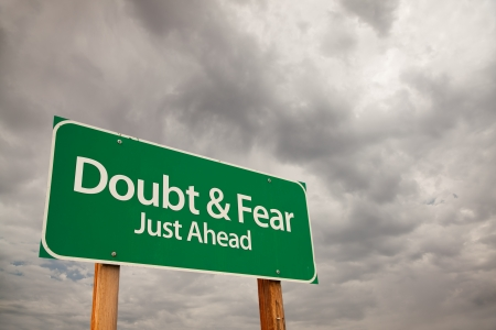 mistrust: Doubt and Fear Just Ahead Green Road Sign with Dramatic Storm Clouds and Sky.