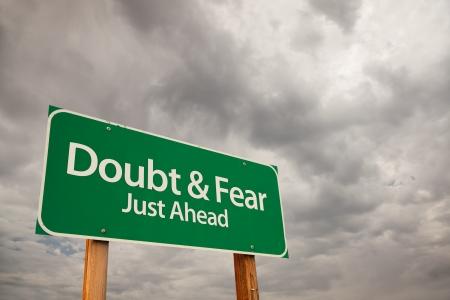 ambivalence: Doute et la peur juste avant le chemin vert signe avec des nuages de temp�te dramatique et le ciel. Banque d'images