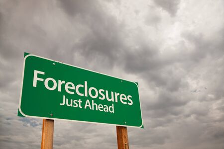 bank owned: Foreclosures Just Ahead Green Road Sign with Dramatic Storm Clouds and Sky.