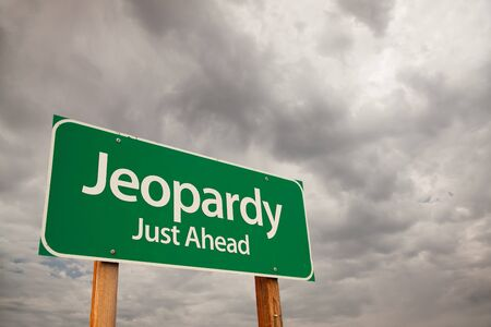 jeopardy: Jeopardy Just Ahead Green Road Sign with Dramatic Storm Clouds and Sky.