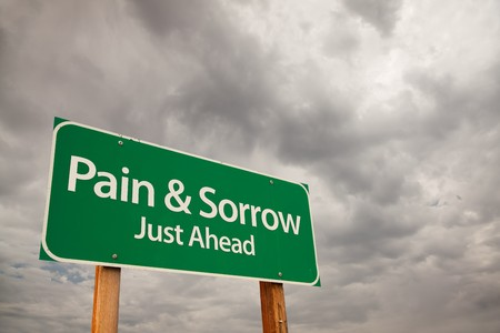 downfall: Pain and Sorrow Just Ahead Green Road Sign with Dramatic Storm Clouds and Sky.