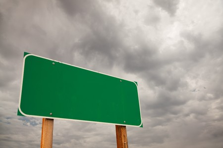 Blank Green Road Sign over Dramatic Stormy Clouds - Ready for your own message and Room For Copy on the Clouds.