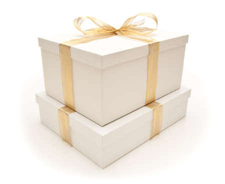 Stacked White Gift Boxes with Gold Ribbon and Bow Isolated on a White Background. photo