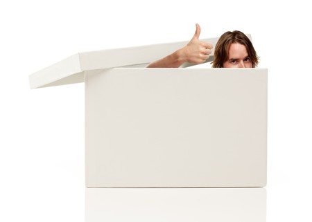 Young Man with Thumbs Up and Popping His Head out from a Blank White Box Isolated on a White Background - Box Ready for Your Own Message. Foto de archivo