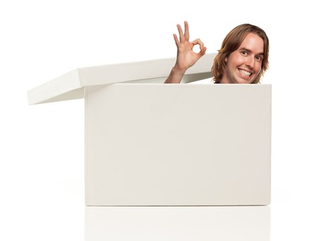 Young Man with Okay Hand Signal and Popping His Head from Blank White Box Isolated on a White Background - Box Ready for Your Own Message. photo