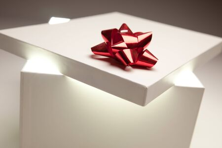 Gift Box with Red Bow Lid Revealing Very Bright Contents on a Gradated Background. photo