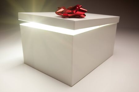 Gift Box with Red Bow Lid Revealing Very Bright Contents on a Gradated Background. Stock Photo - 7419957