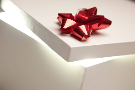 Gift Box with Red Bow Lid Revealing Very Bright Contents on a Gradated Background.