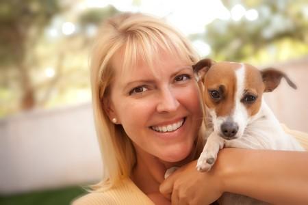 woman with dog: Mujer atractiva y su perro Jack Russell Terrier al aire libre con enfoque selectivo.