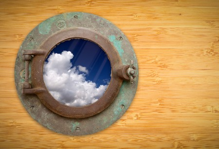 Antique Porthole on Bamboo Wall with View of Beautiful Blue Sky and Clouds. photo