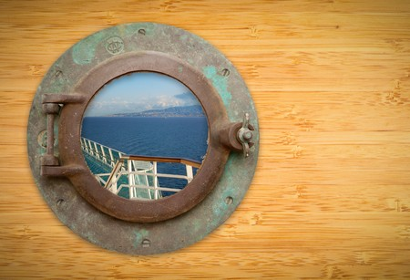 Antique Porthole on Bamboo Wall with View of Ship Deck Railing, Ocean, Land and Sky. photo