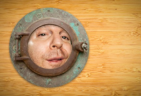 Antique Porthole on Bamboo Wall with Funky Man Looking Through the Window. photo