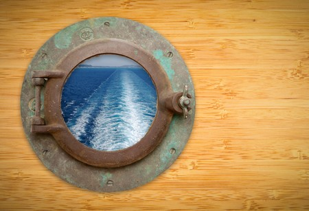 Antique Porthole on Bamboo Wall with View of Ship Wave Trail, Land and Sky. photo