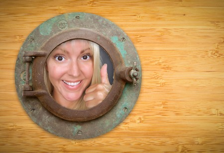 Antique Porthole on Bamboo Wall, Woman with Thumbs Up Looking Through Window. photo