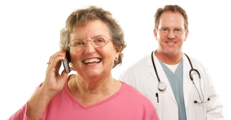 Happy Senior Woman Using Cell Phone with Male Doctor or Nurse Behind Isolated on a White Background. photo