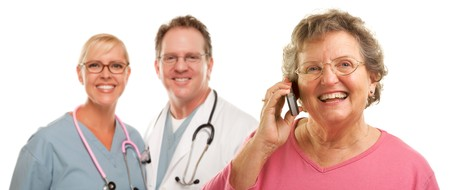 Happy Senior Woman Using Cell Phone with Male and Female Doctors or Nurses Behind Isolated on a White Background. photo
