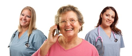 Happy Senior Woman Using Cell Phone with Female Doctors or Nurses Behind Isolated on a White Background. photo