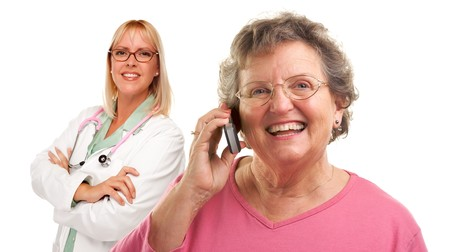 Happy Senior Woman Using Cell Phone with Female Doctor or Nurse Behind Isolated on a White Background.. photo