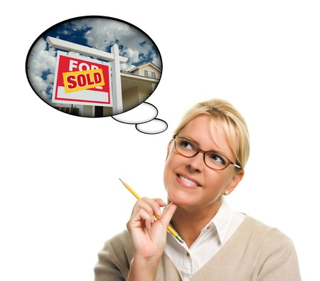 Woman with Thought Bubbles of a Sold Real Estate Sign to a New Home Isolated on a White Background. photo