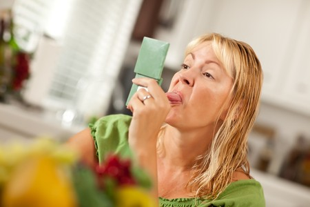 Blonde Woman Sticking Her Tongue Out at Herself in a Compact Mirror. photo