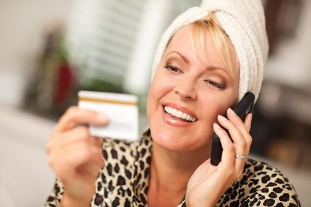 robbed: Smiling Robed Woman on Cell Phone Looking At Her Credit Card.