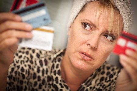 Upset Robed Woman Glaring At Her Many Credit Cards. Stock Photo - 7872997