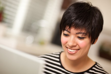Pretty Smiling Multiethnic Woman Using Her Laptop Computer. photo