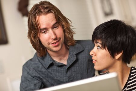 Happy Young Caucasian Man and Multiethnic Woman Using the Laptop Computer Together. Stock Photo - 7873001