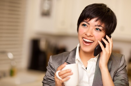 Pretty Smiling Multiethnic Woman with Coffee and Talking on a Cell Phone in Her Kitchen. photo