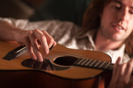 Young Musician Plays His Acoustic Guitar under Dramatic Lighting. photo