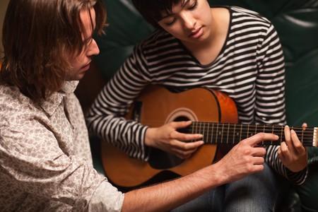 若い男性ミュージシャンは女性学生を教えるどのようにギターをプレイします。